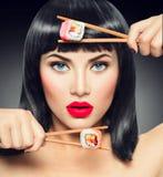 Sushi. Beauty model girl eating sushi rolls Stock Photo