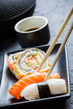 Sushi in a black ceramic eaten with chopsticks Royalty Free Stock Photos