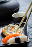 Sushi in a black ceramic eaten with chopsticks Royalty Free Stock Photography