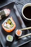 Sushi on black ceramic eaten with chopsticks Royalty Free Stock Photos