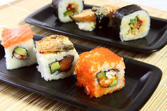 Sushi in black ceramics. Six sushi on black ceramic plates Royalty Free Stock Photo