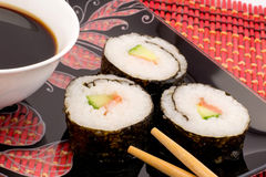 Sushi on a black plate on a red mat with chopsticks and  soy sauce Royalty Free Stock Images