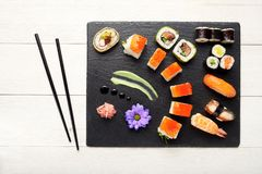 Sushi on black stone plate isolated. Top view stock images
