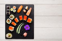 Sushi on black stone plate on a wooden table Royalty Free Stock Image