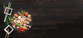Sushi on a black wooden surface.  Royalty Free Stock Photography