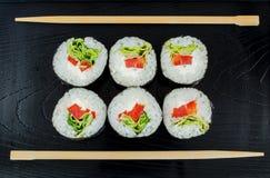 Sushi on a black wooden tray, chopsticks Stock Photos