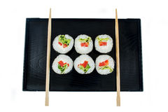 Sushi on a black wooden tray with chopsticks isolated Stock Photography