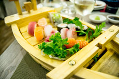 Sushi boat with variety of sushi pieces with green salad Royalty Free Stock Images