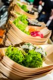 Sushi boats with green garnish. Rows of bamboo boats with green salad garnish, wasabi and sushi rolls. Catering luxury party royalty free stock images