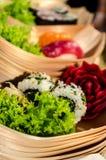 Sushi boats with sushi and garnish. Rows of bamboo boats with sushi and beautiful garnish. Maki and Nigiri sushi elegant presentation for luxurious party stock photos