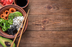 Sushi bowl on the wooden background. Sushi bowl with seaweed, avocado, radishes, cucumber and black sesame seeds Royalty Free Stock Photography