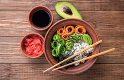 Sushi bowl on the wooden background. Sushi bowl with seaweed, avocado, radishes, cucumber and black sesame seeds Royalty Free Stock Image