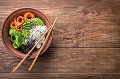 Sushi bowl on the wooden background. Sushi bowl with seaweed, avocado, radishes, cucumber and black sesame seeds Stock Photos