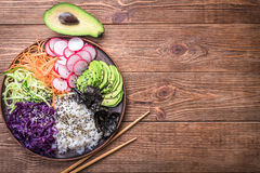 Sushi bowl on the wooden background. Sushi bowl with seaweed, avocado, radishes, cucumber, carrot red cabbage, and black sesame seeds Stock Photography