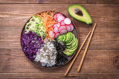 Sushi bowl on the wooden background. Sushi bowl with seaweed, avocado, radishes, cucumber, carrot red cabbage, and black sesame seeds Royalty Free Stock Photos