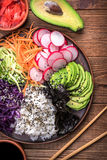 Sushi bowl on the wooden background. Sushi bowl with seaweed, avocado, radishes, cucumber, carrot red cabbage, and black sesame seeds Royalty Free Stock Photography