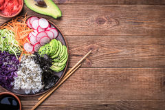 Sushi bowl on the wooden background. Sushi bowl with seaweed, avocado, radishes, cucumber, carrot red cabbage, and black sesame seeds Royalty Free Stock Photo