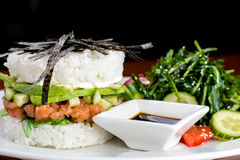 Sushi Burger with salmon and salad with soy souce. Sushi burger with salmon, avocado, cucumber and fresh salads with soy sauce Stock Images