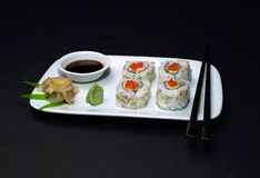 Sushi - California Roll. Sushi, a California Roll with wasabi, soy sauce, ginger, and chopsticks, presented artfully Stock Photo