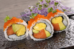 Sushi california roll. California roll sushi with caviar on a black plate Stock Image