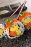 Sushi california roll. California roll sushi with caviar on a black plate Royalty Free Stock Image
