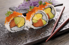 Sushi california roll. California roll sushi with caviar and chopsticks on a black plate Stock Photography