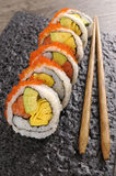 Sushi california roll. California roll sushi with caviar and chopsticks on a black plate Royalty Free Stock Images