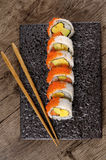 Sushi california roll with chopsticks on black plate Stock Photo