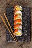Sushi california roll with chopsticks on black plate. California roll sushi with caviar and chopsticks on black plate Stock Photo