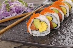 Sushi california roll with chopsticks on black plate. California roll sushi with caviar and chopsticks on  black plate Royalty Free Stock Image