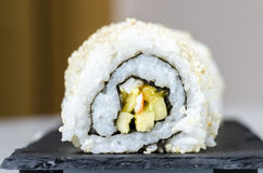 Sushi, california roll with sesame seeds. Sushi, california roll with sesame seeds on a slate plate Royalty Free Stock Images