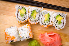 Sushi California rolls appetizer with rice avocado with chopsticks. California rolls appetizer with rice avocado with chopsticks. Sushi is often prepared with royalty free stock photo