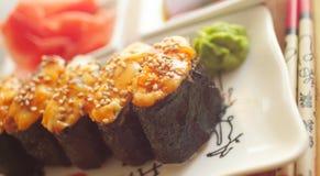 Sushi chauds de plaque avec des baguettes Photographie stock libre de droits