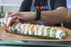 Sushi chef plating a roll of sushi. Sushi chef plating a rainbow roll of sushi at a restaurant Stock Photo