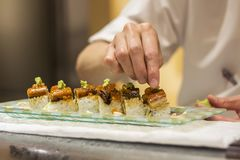 Sushi chef preparing eel maki roll for customer in a sushi bar. An itamae or sushi chef topping wasabi over a maki roll with eel, salmon roe, egg served in a royalty free stock photos