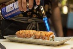 Sushi chef preparing maki sushi roll with torch burner, firing direct towards smoke salmon in the kitchen of izakaya. An itamae or sushi chef preparing maki stock photos