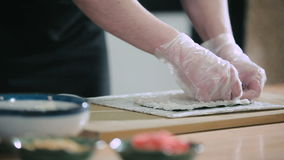 Sushi chef preparing rice for sushi roll. Cooking sushi rolls. Square roll of rice, shrimp and nori stock video footage
