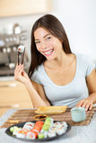Sushi chopstick holding young smiling Asian female Royalty Free Stock Image