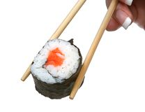 Sushi between chopsticks Royalty Free Stock Photo