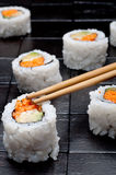 Sushi with chopsticks on back wood Stock Photography