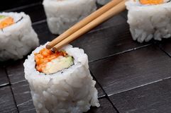 Sushi with chopsticks on a black background Stock Images