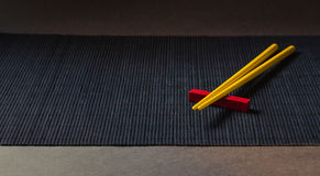 Sushi chopsticks on black bamboo straw mat Stock Images