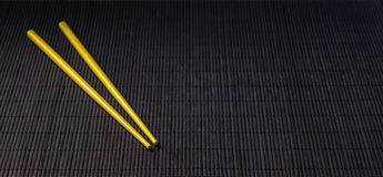 Sushi chopsticks on black bamboo straw mat Stock Image
