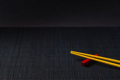Sushi chopsticks on black bamboo straw mat Stock Photos