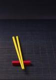Sushi chopsticks on black bamboo straw mat Stock Photos