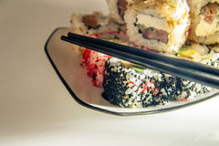 Sushi and chopsticks. Lying on a white plate Royalty Free Stock Images