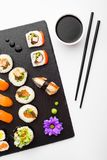 Sushi, chopsticks and soy sauce on black stone plate Royalty Free Stock Photos