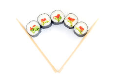 Sushi between chopsticks for sushi isolated on white. Top view. Royalty Free Stock Photos
