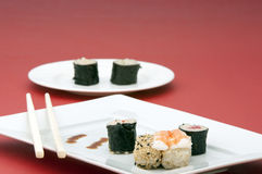 Sushi and chopstics on plate. A selection of sushi and a pair of chopstics on a white rectangular plate with second plate OOF Royalty Free Stock Images