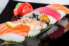 Sushi cinco en la hoja de bambú Foto de archivo libre de regalías